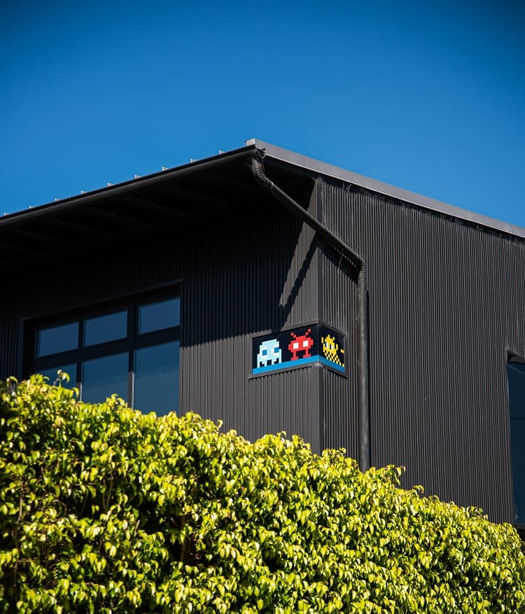 exterior of a warehouse-like home in Venica, CA with artwork by french artist Invader.