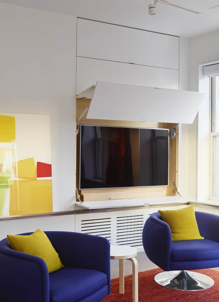 clever design hides the TV into the wall of the apartment