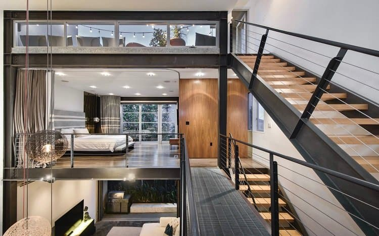 The two-story loft's bedrooms are suspended over the living room