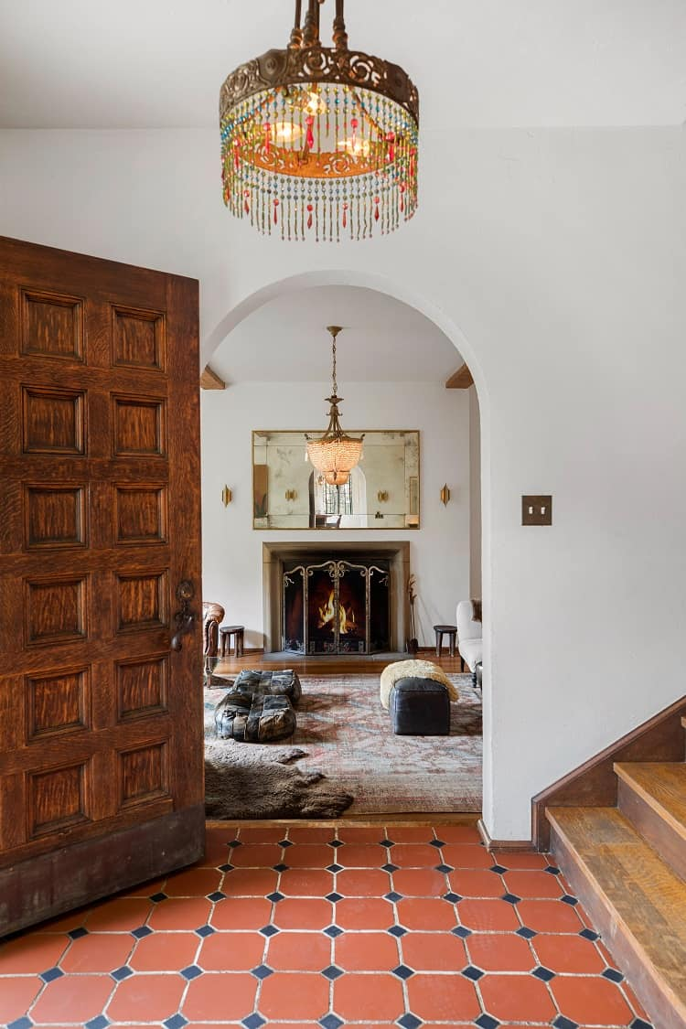 The foyer leads into the formal living room, which has its original stone wood-burning fireplace.