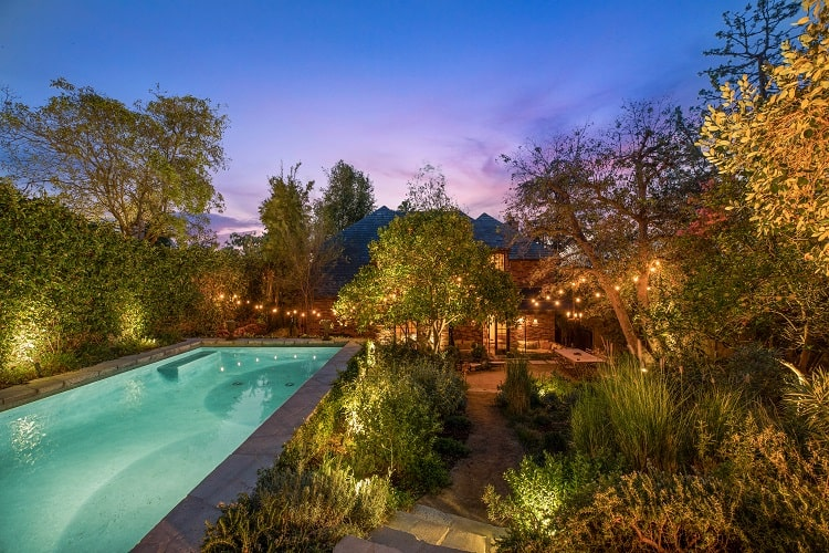 Walton Goggins' house has a whimsical backyard with two outdoor dining areas, a pool, and a fire pit.