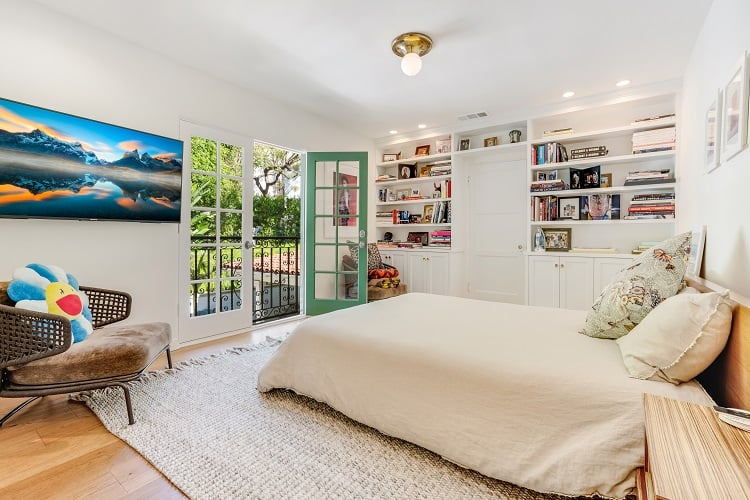 secondary bedroom with balcony and built-in bookshelves