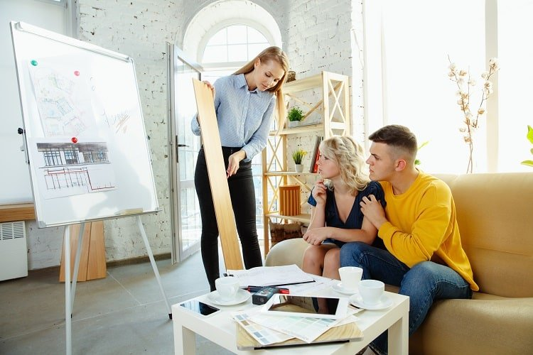 Interior designer working with young couple. Lovely family and professional designer discussing concept of future interior, working with color palette, room drawings in modern office.
