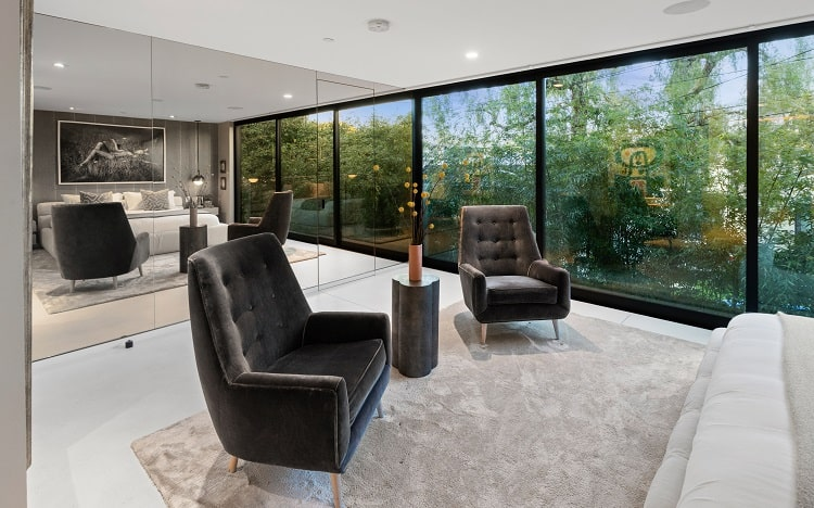 A glass-clad wall in the main bedroom masks a walk-in closet and reflects the outdoor views.