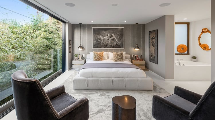 The inviting main bedroom has walls of glass opening up to nature views that also bring in plenty of natural light.