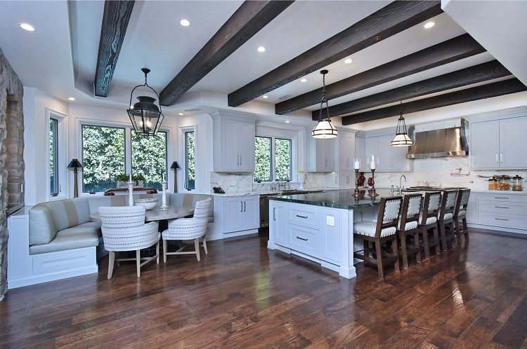 luxury white kitchen with warm wood floors, wooden beams and a lovely breakfast nook