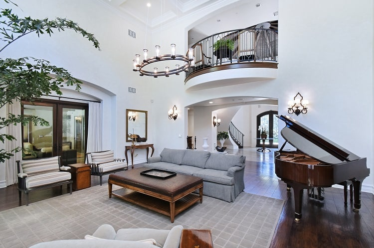 majestic two-story living room with a piano and balcony