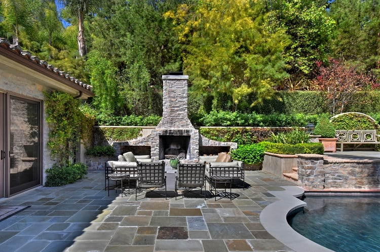 beautiful backyard with a stone fireplace next to the pool