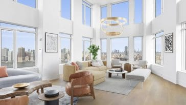 a light-filled penthouse living room with tall ceilings and double-height windows