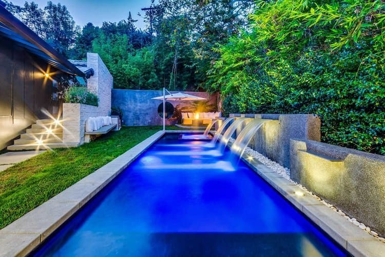 The secluded pool area is surrounded by trees and has waterfalls, a dining deck with firepit and a barbecue island.